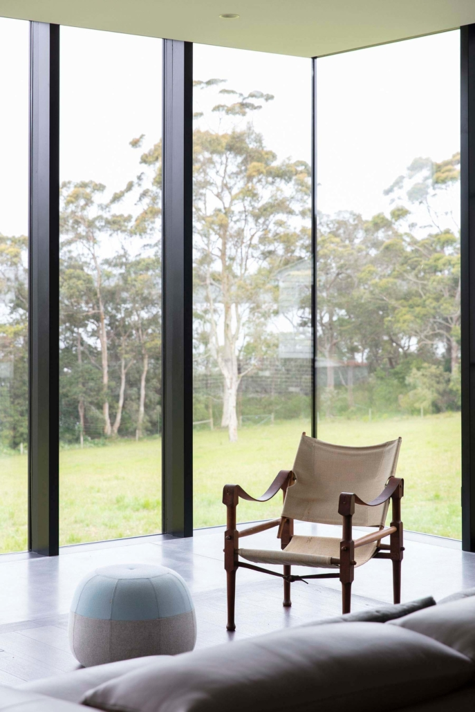 chair and ottoman in front of floor to ceiling window overlooking trees