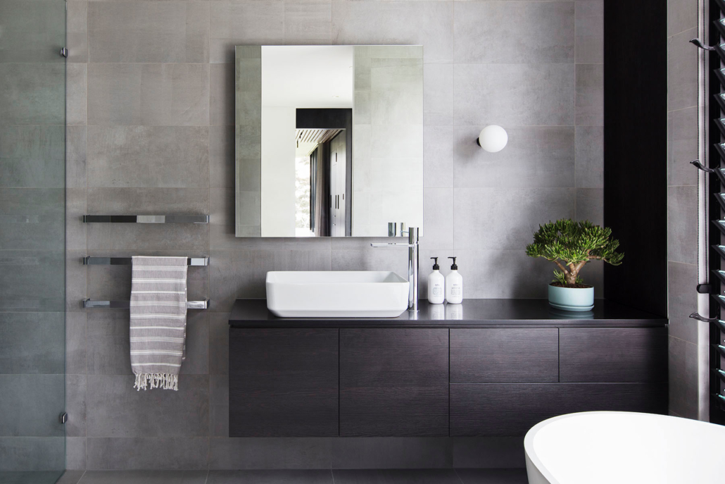 minimalist bathroom sink area with grey slate tiles and dark timber cabinetry