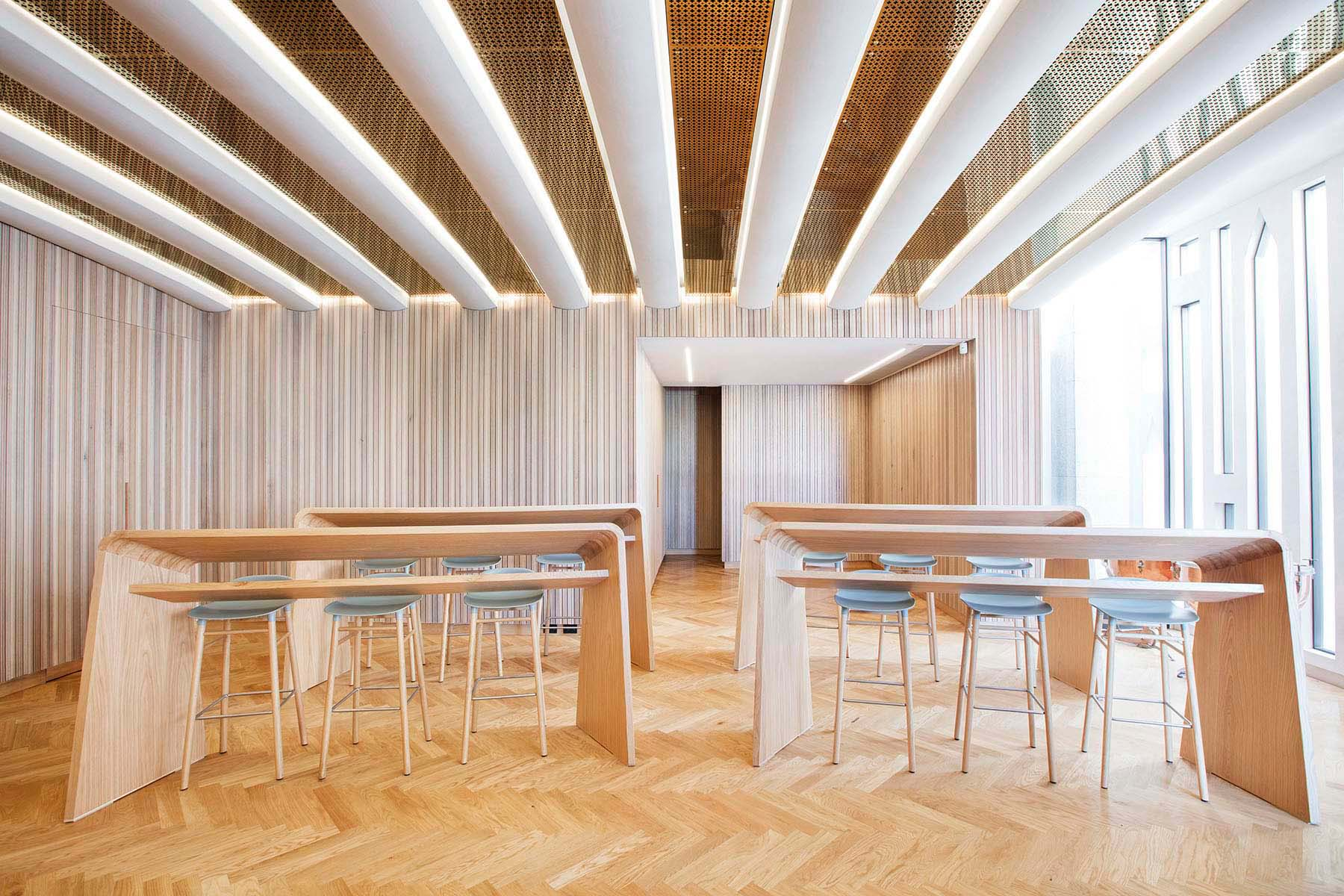 symmetrical interior of room made from vertical timber with chared desks and stools