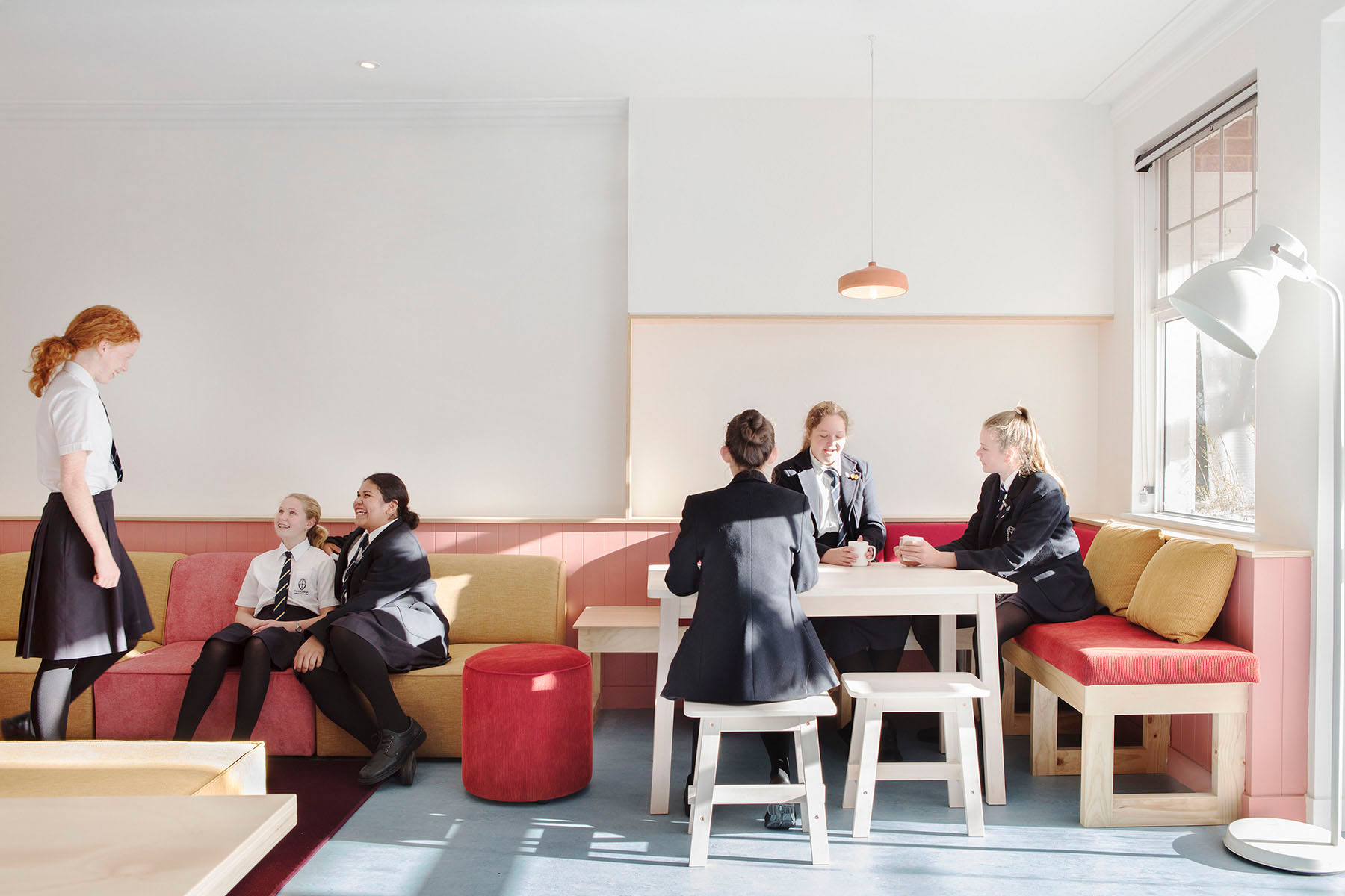 group of girls in school uniform talking at a table and couch area