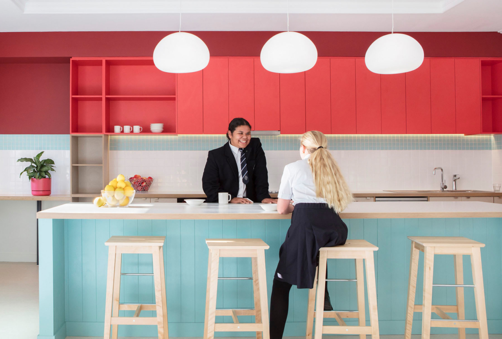 two girls in school uniform in a brightly coloured kitchen area