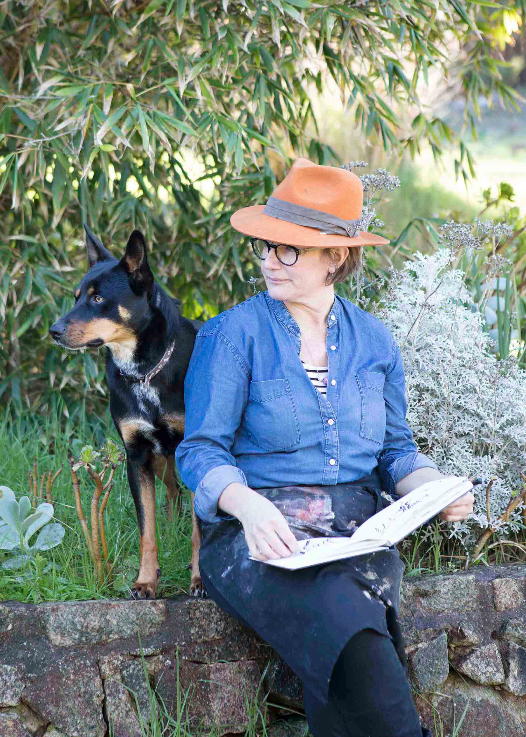 woman with orange hat sits to draw in an open book with her dog beside her