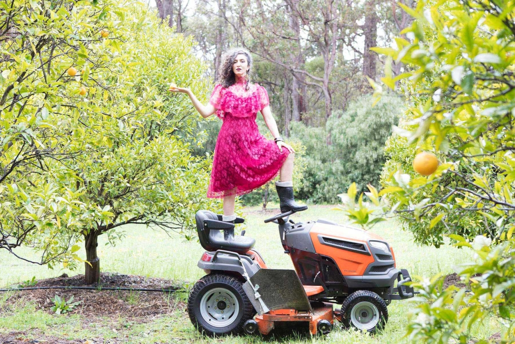 woman in a dress and gumboots standing on a ride on mower in an orange orchard.
