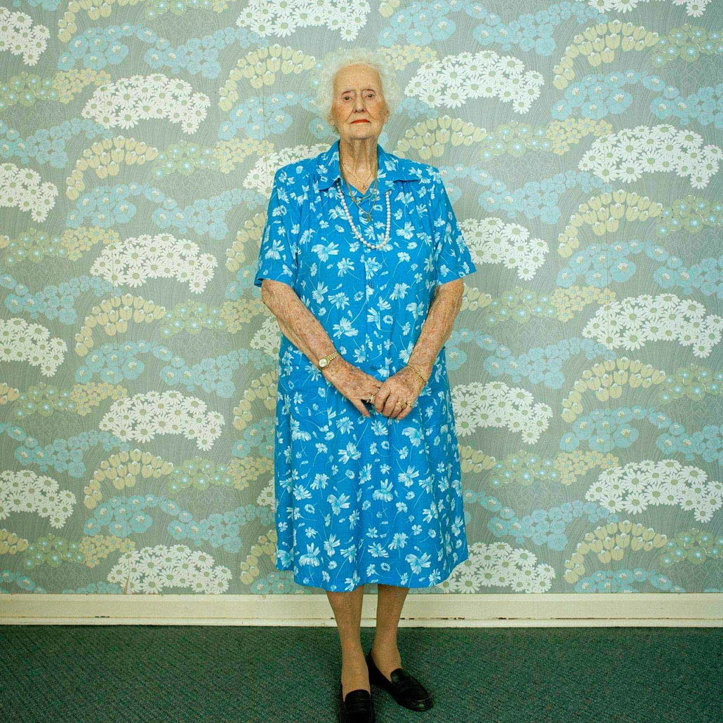 elderly woman in a floral dress standing in front of floral wallpaper